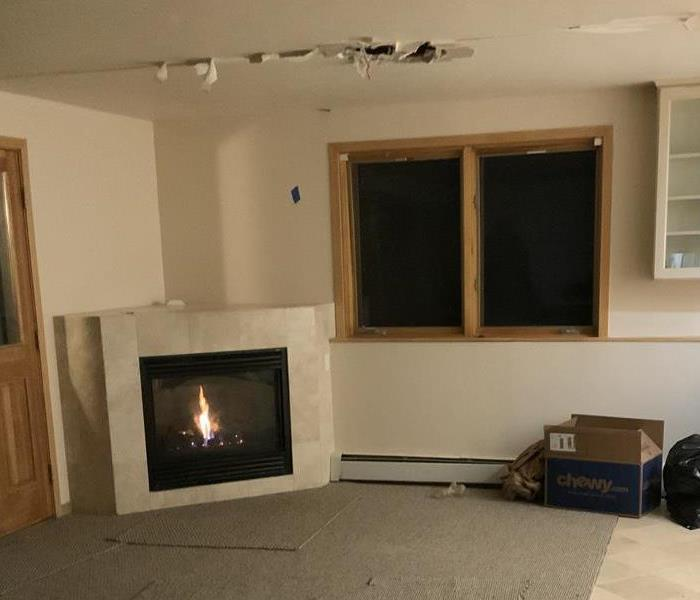 Living room with a hole in the ceiling.