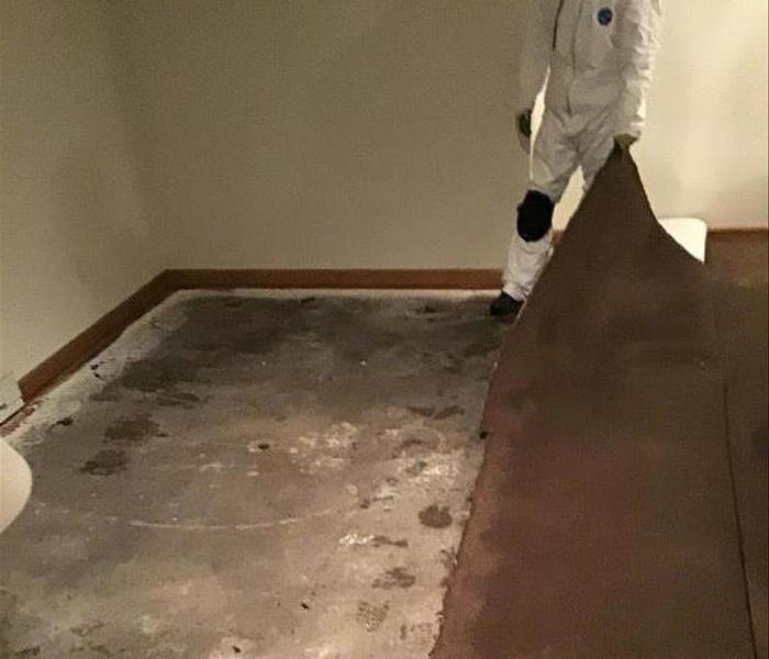 Concrete is exposed while the carpet is pulled back.