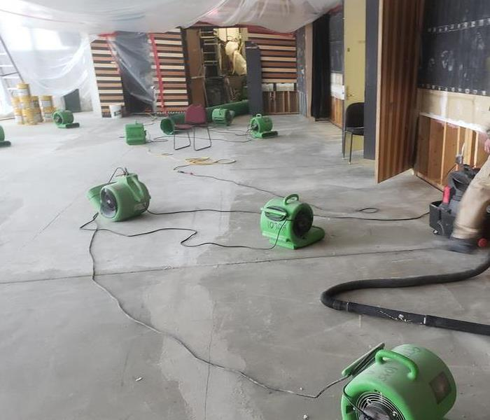 Garage floor covered in green air movers.