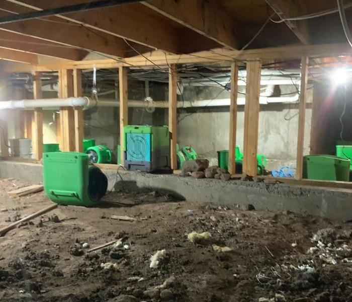 The underneath of a building with green SERVPRO equipment.