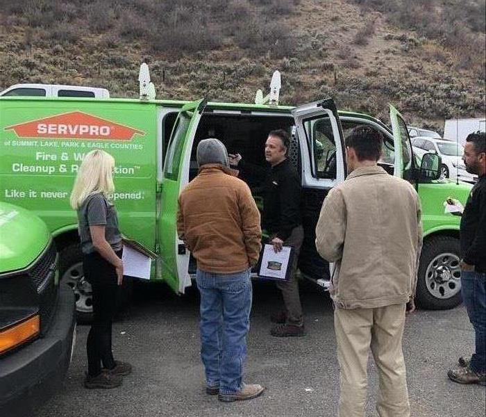 Employees standing outside a green SERVPRO van.