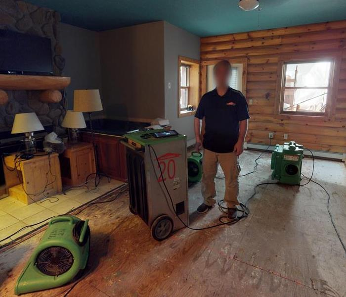 Room filled with green air movers, and raw exposed wood on the walls and floor.
