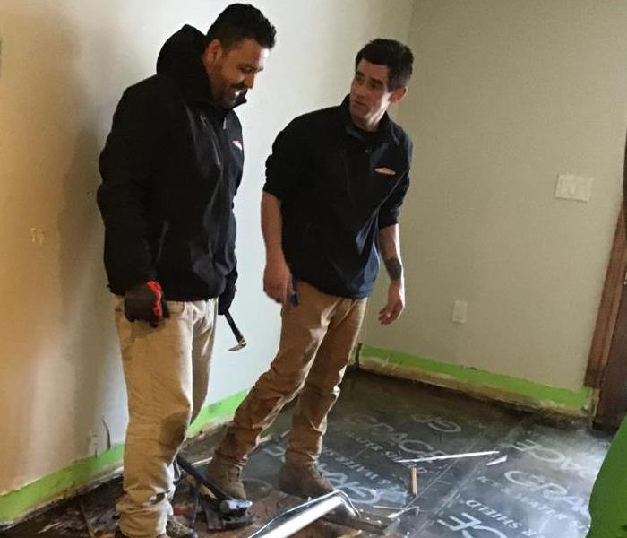 two employees working on removing a water damaged floor.