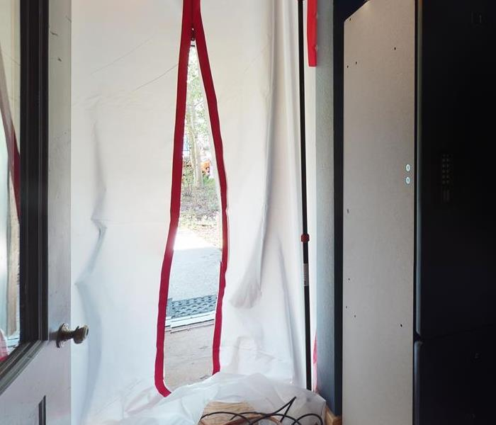 White sheet with red tape securing an area.