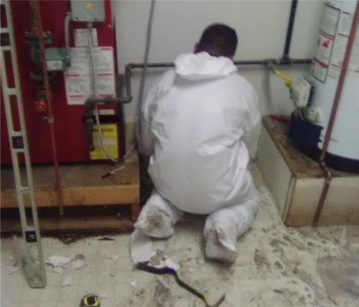 Technician wearing protective gear, on his knees fixing a water heater