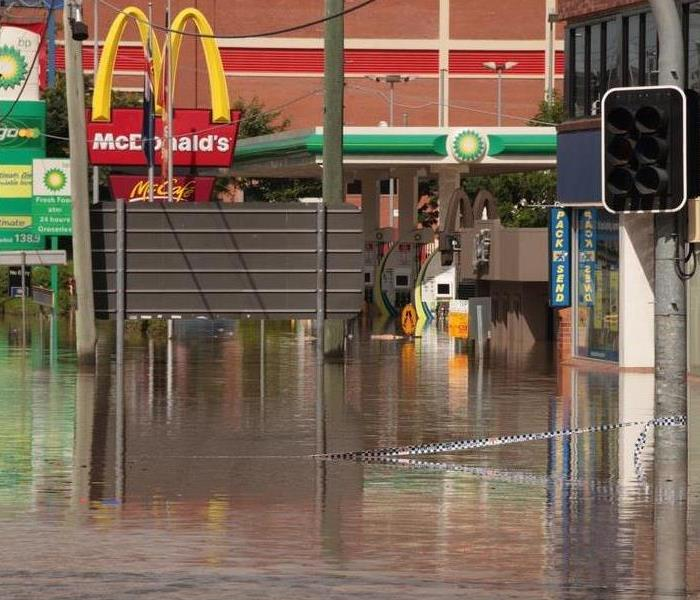 Flood waters rising over business such as a McDonalds in the background.